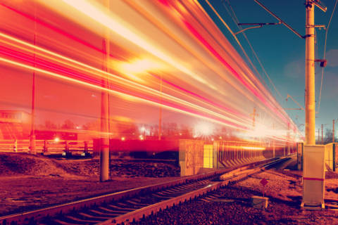 Long exposure photo of a train speeding down the train tracks in a desolate area at night time