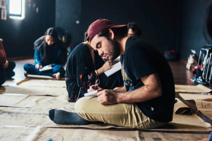 A man sits on the floor and writes in his notebook