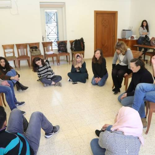 People are gathered in a circle - some sit on chairs and some sit on floors - in discussion.