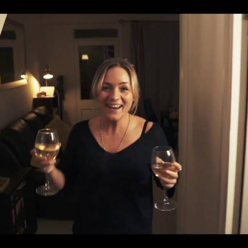 A woman holding 2 glasses of wine