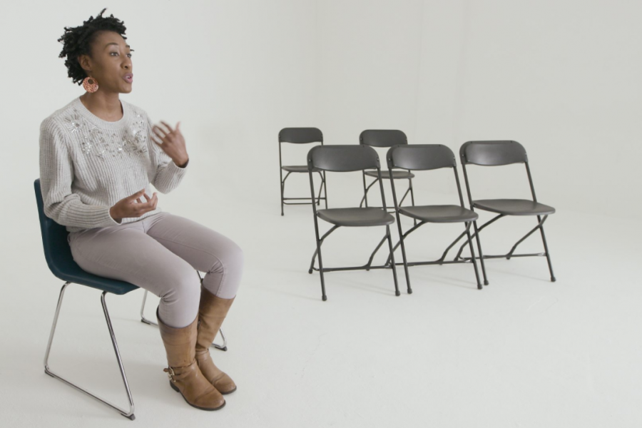 A woman sits on a lone chair, with a row of three chairs behind her at a distance