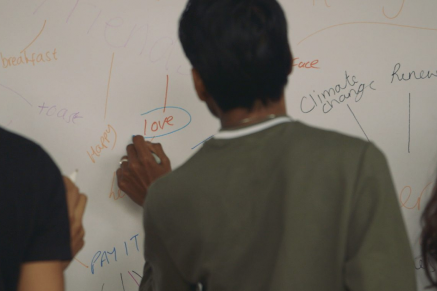 A man with his back to the viewer writes on a whiteboard